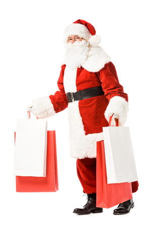 santa claus walking with paper bags in hands isolated on white
