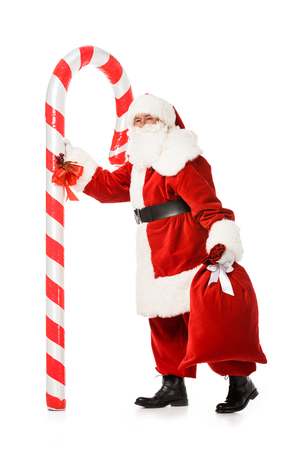 santa claus with giant candy cane and sack walking isolated on white Banco de Imagens