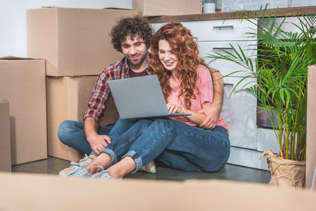 couple hugging and sitting with laptop near cardboard boxes on floor in new kitchen