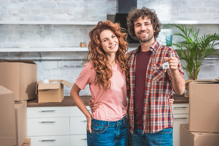 smiling couple hugging and holding house trinket with keys at new home