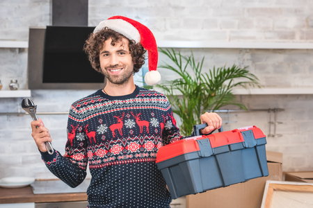happy young man in santa hat holding toolbox and smiling at camera in new apartment Stock Photo
