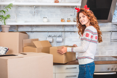 happy young woman in antlers headband unpacking cardboard boxes and smiling at camera during relocation