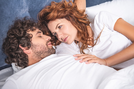 smiling young woman looking at boyfriend sleeping on bed