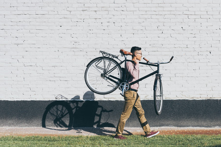 side view of asian man carrying bicycle while walking on street Banque d'images - 112355254