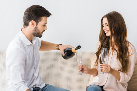 young man pouring champagne into glass while sitting on couch with girlfriend at home Stockfoto