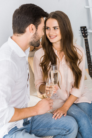 happy couple clinking glasses of champagne on sofa at new home Banco de Imagens - 111745358