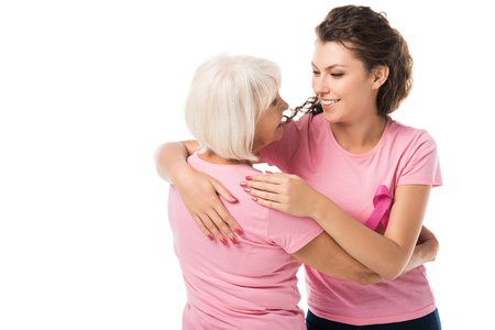 women in pink t-shirts hugging and smiling each other isolated on white, breast cancer awareness concept Archivio Fotografico