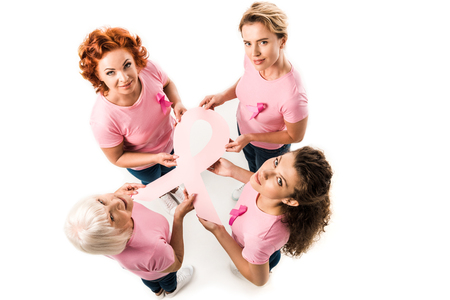 overhead view of women in pink t-shirts holding breast cancer awareness ribbon and smiling at camera isolated on white