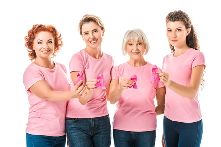 women in pink t-shirts holding breast cancer awareness ribbons and smiling at camera isolated on white Фото со стока