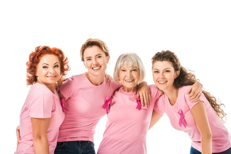 cheerful women in pink t-shirts with cancer awareness ribbons smiling at camera isolated on white