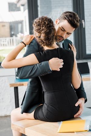 passionate businessman unzipping dress of seductive businesswoman at workplace in office Standard-Bild