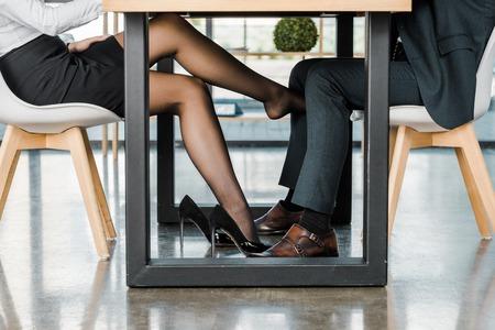 Abgeschnittene Aufnahme einer Geschäftsfrau, die während der Arbeit im Büro mit einem Geschäftsmann flirtet