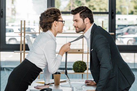 side view of businessman and businesswoman flirting at workplace in office