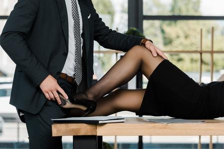 gedeeltelijke weergave van gepassioneerde zakenman en zakenvrouw op de werkplek op kantoor Stockfoto