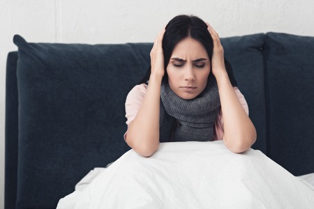 sick young woman sitting in bed and holding head during headache 스톡 콘텐츠