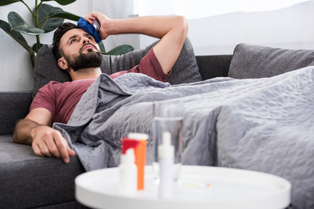 sick young man lying on couch and holding ice pack on forehead