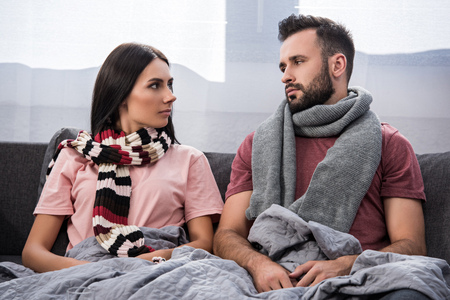 sick young couple sitting on couch and looking at each other