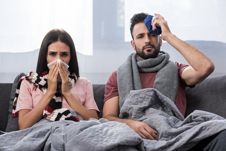 sick young couple with napkin and ice pack sitting together on couch and looking at camera Stockfoto - 111171677