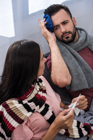 diseased young couple with electric thermometer and ice pack sitting together on couch Stockfoto