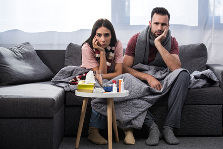 diseased young couple with meds on table sitting together on couch Stockfoto - 110962502