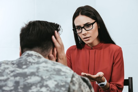 female psychiatrist talking to depressed soldier with ptsd during therapy session