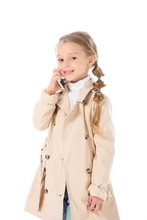 adorable child in autumn beige coat talking on smartphone, isolated on white Stok Fotoğraf