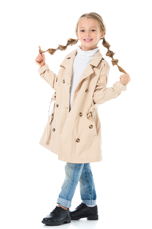 adorable blonde kid with braids posing in beige coat, isolated on white