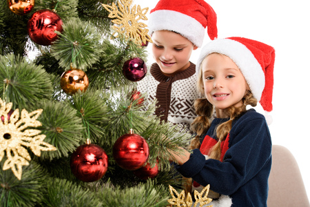 happy siblings in santa hat decorating christmas tree with balls