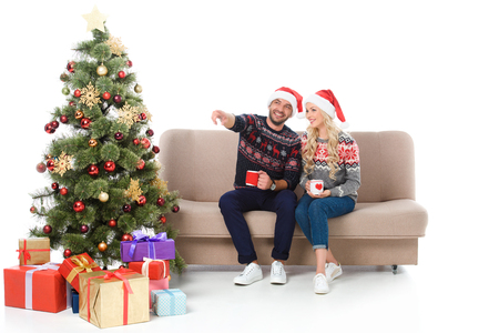 beautiful couple with cups of coffee and sitting on sofa near christmas tree with gifts, man pointing somewhere, isolated on white Standard-Bild - 111171736