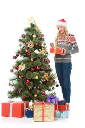beautiful happy woman putting presents under christmas tree, isolated on white Stock Photo