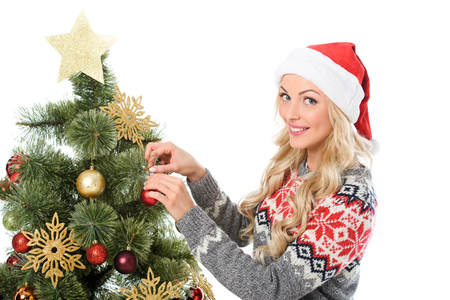 beautiful woman in santa hat decorating christmas tree, isolated on white