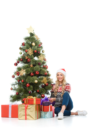 beautiful woman putting gift boxes under christmas tree, isolated on white Stock Photo