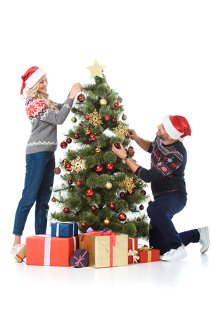 happy couple in santa hats decorating christmas tree with presents, isolated on white Stock Photo