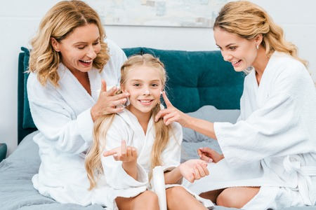 happy child with mother and grandmother in bathrobes sitting on bed at home and applying moisturizing cream
