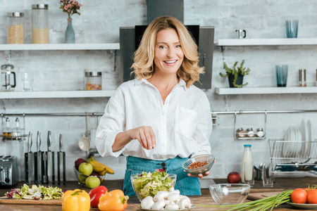 beautiful adult woman spilling spice onto lettuce in bowl at kitchen and looking at camera Stockfoto