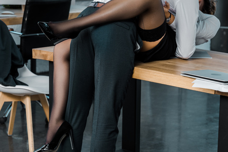 cropped shot of passionate sexy businesswoman and businessman at workplace in office