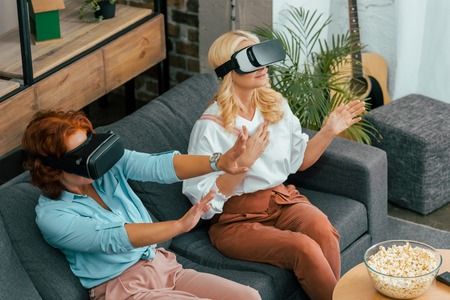 high angle view of mature women sitting on couch and using virtual reality headsets Banco de Imagens