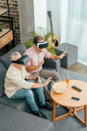 high angle view of mature men drinking beer and using virtual reality headsets while sitting on couch