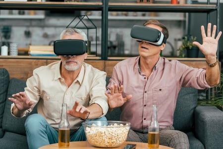 handsome mature male friends sitting on couch and using virtual reality headsets Stok Fotoğraf