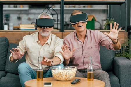 happy mature men sitting on couch and using virtual reality headsets Banco de Imagens