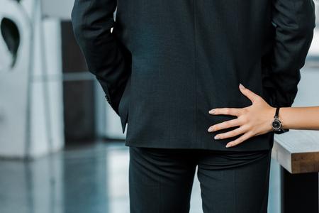 Abgeschnittene Aufnahme einer Geschäftsfrau, die mit einem Kollegen im Büro flirtet