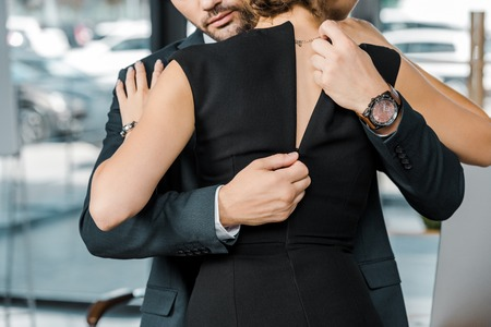 partial view of businessman unzipping dress of seductive businesswoman in office