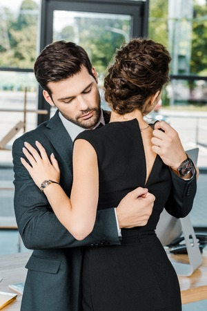 junger Geschäftsmann entpackt Kleid der verführerischen Geschäftsfrau am Arbeitsplatz im Büro un
