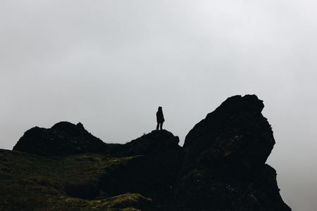 silhouette of woman standing on rock in front of cloudy sky