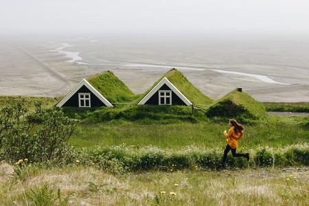 Vue lointaine de jeune femme tournant près de fermes noires dans le parc national de Skaftafell en Islande Banque d'images