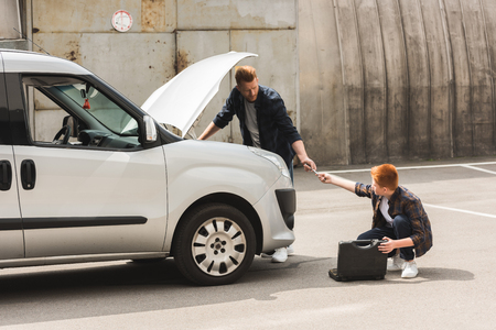 side view of ginger hair son giving tool for repairing car to father