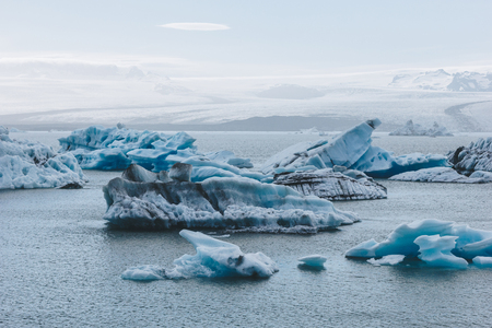 blue ice pieces floating in lake in Jokulsarlon, Iceland under blue sky with mountains on background Reklamní fotografie