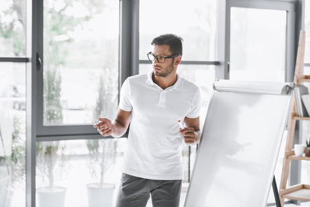 concentrated businessman making presentation at white board in office
