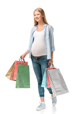 attractive smiling pregnant woman holding shopping bags isolated on white Foto de archivo - 109837601