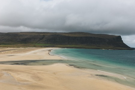dramatic shot of sandy beach and blue ocean with mountain in Iceland under stormy sky